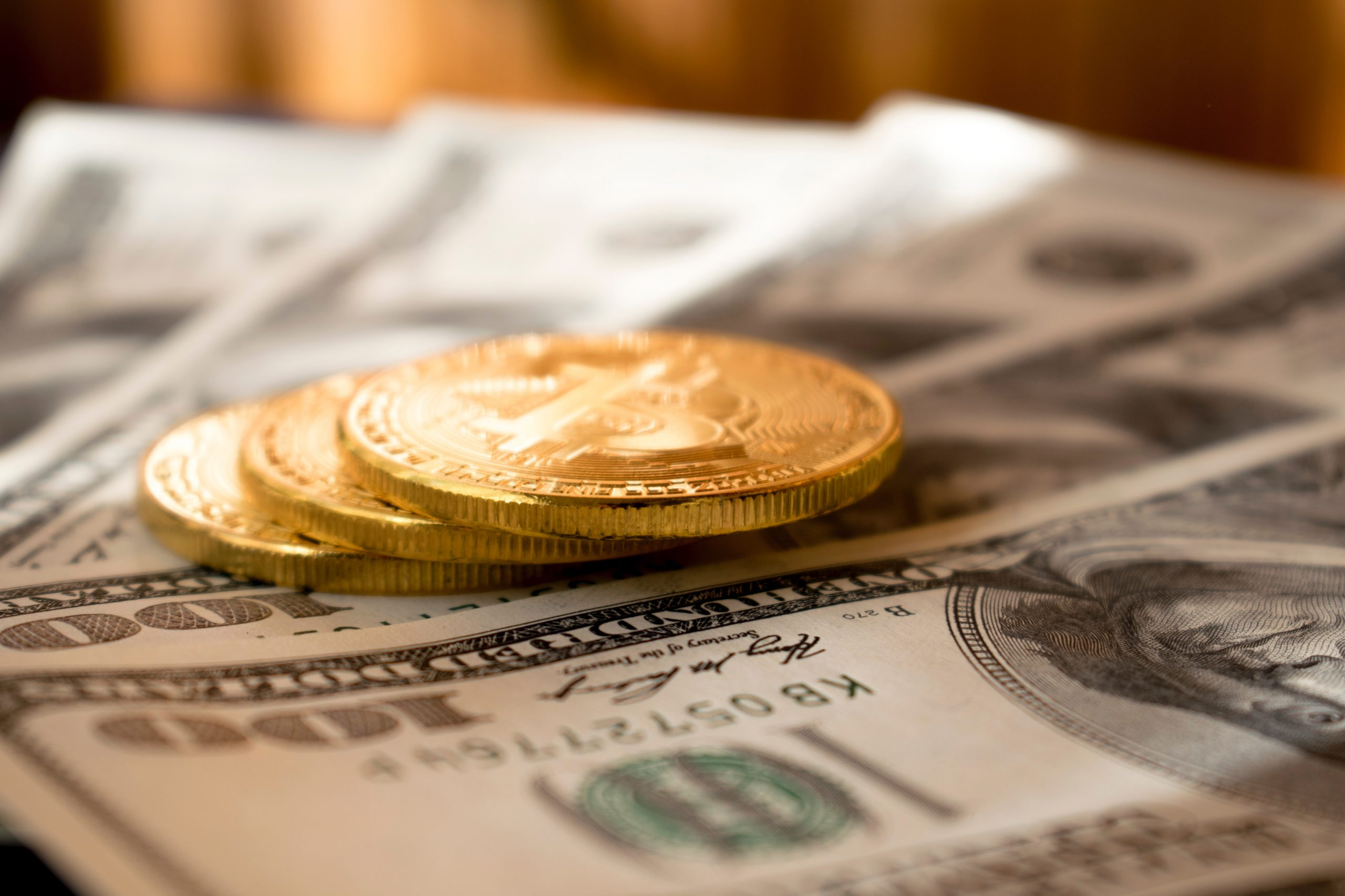 three round gold-colored coins on 100 US dollar banknotes